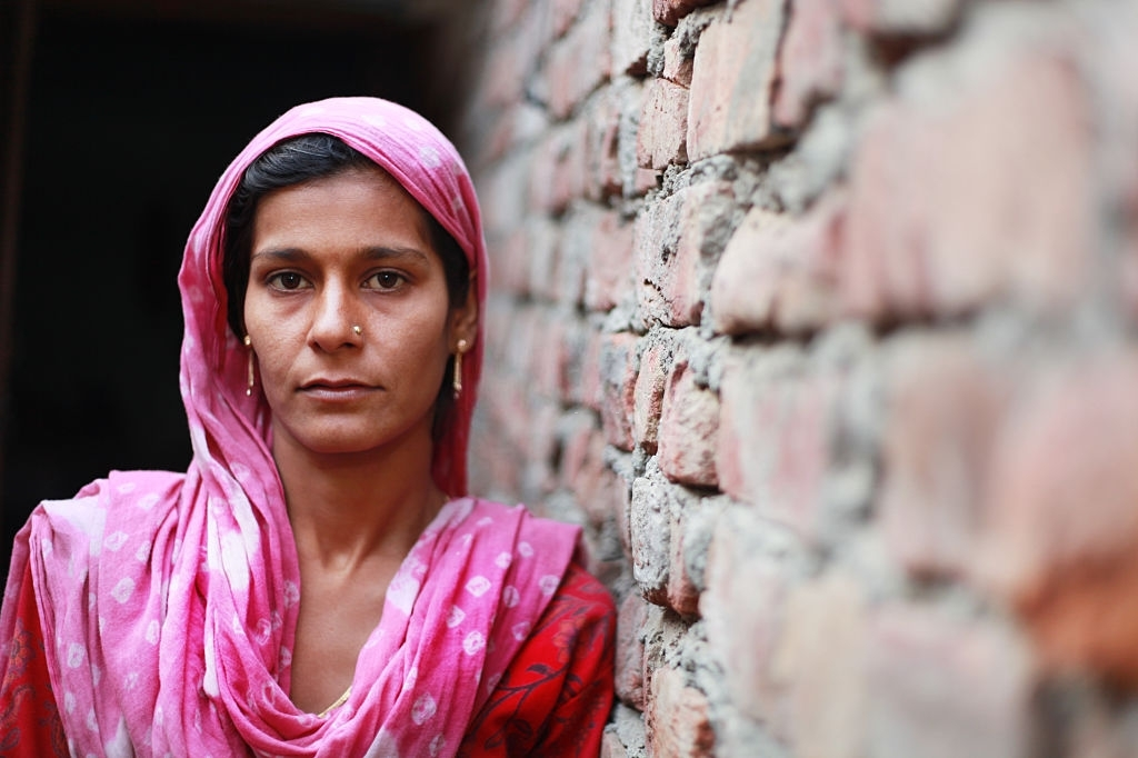Middle aged poor rural women of Indian ethnicity wearing traditional dress and standing against brick wall. She is looking at camera.